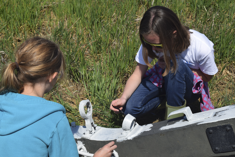 Six-to-Fix volunteers at Antietam re-painting a historic cannon carriage.