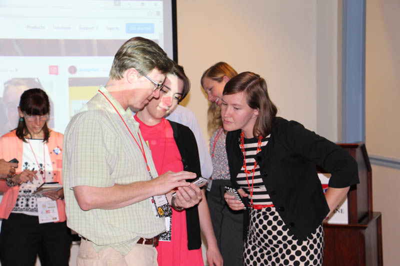 Johns Hopkins, Baltimore Heritage, Emily Huebner, and Auni Gelles (left), Heart of the Civil War Heritage Area, examining a cell phone at the social media presentation.