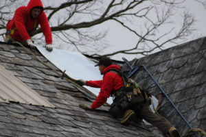 Durable Slate roofers attach temporary patches to the historic farmhouse
