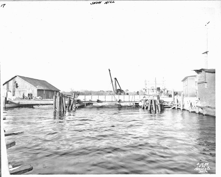 View of the west elevation of the concrete bridge during construction. At left, workers place wire mesh around the steel beams before they are encased in concrete. The piles at either side of the bascule leaf are placed to protect the span from impact. Sanborn Fire Insurance Maps identify the building at left as a fertilizer warehouse. Photo from the Maryland Department of Transportation.