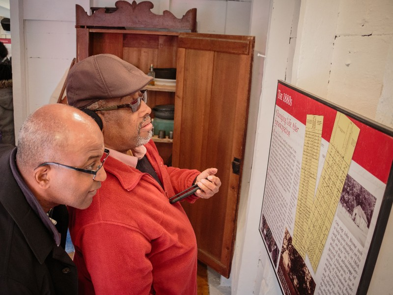 Visitors explore the Brome Slave Cabin exhibit. Photo from Historic St. Mary's City.