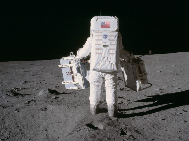 Astronaut Buzz Aldrin carries in his right hand the mirror array designed by UMD physicists. Photo from NASA.