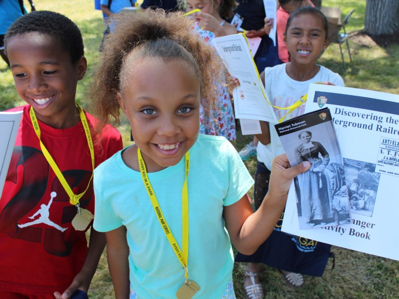 A student shows her junior ranger activity book at Harriet Tubman National Monument. Photo from NPS.