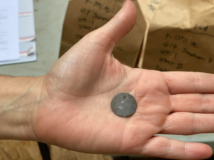 Pierced dime located in Jonathan Street excavation, 2020.