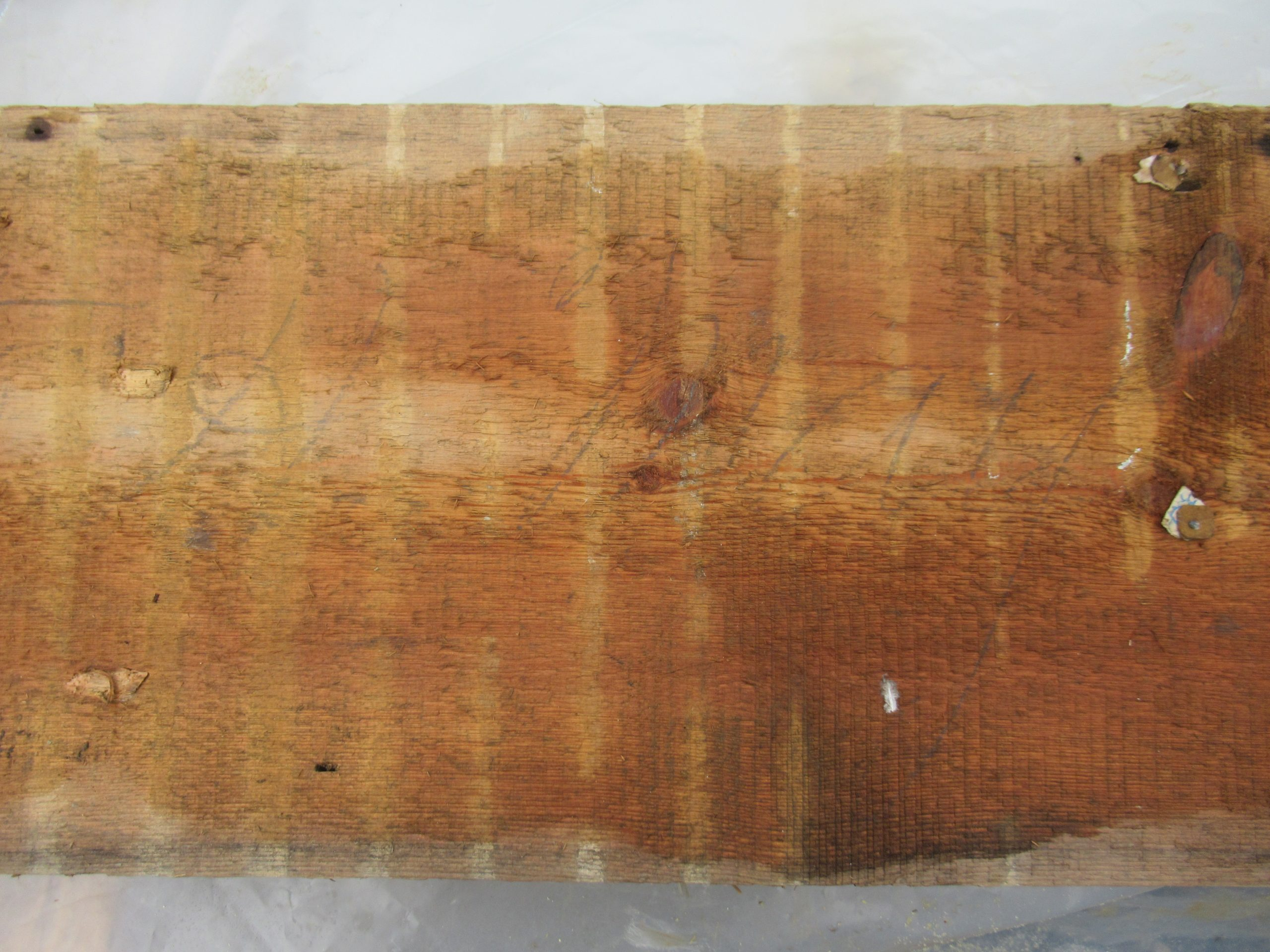 """A piece of the cabin wall with faded cursive that read, """"Sold to H May."""""""