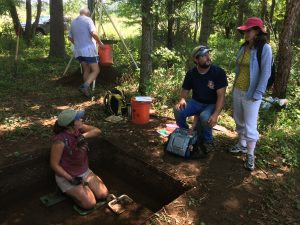Former Interns visit an archeological dig site.