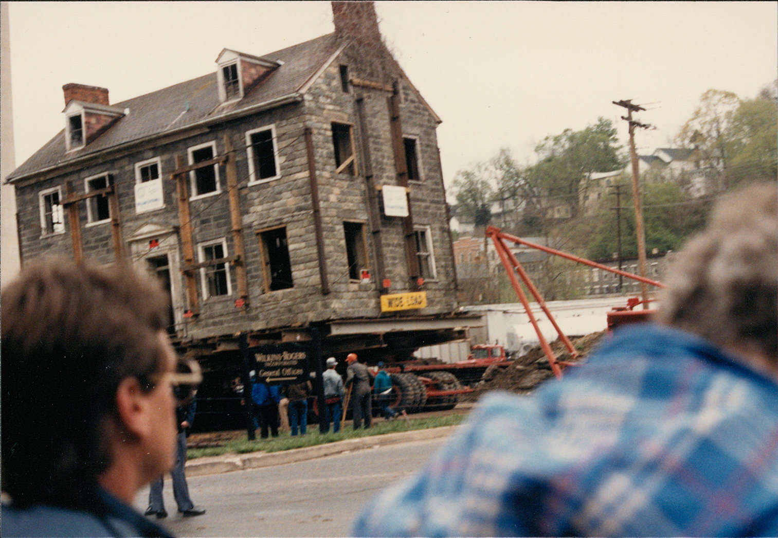 Exterior shot of the George Ellicott House in Oella, MD being moved to higher ground following Hurricane Agnes, in 1987. Scanned from the Preservation Maryland physical photograph collection.