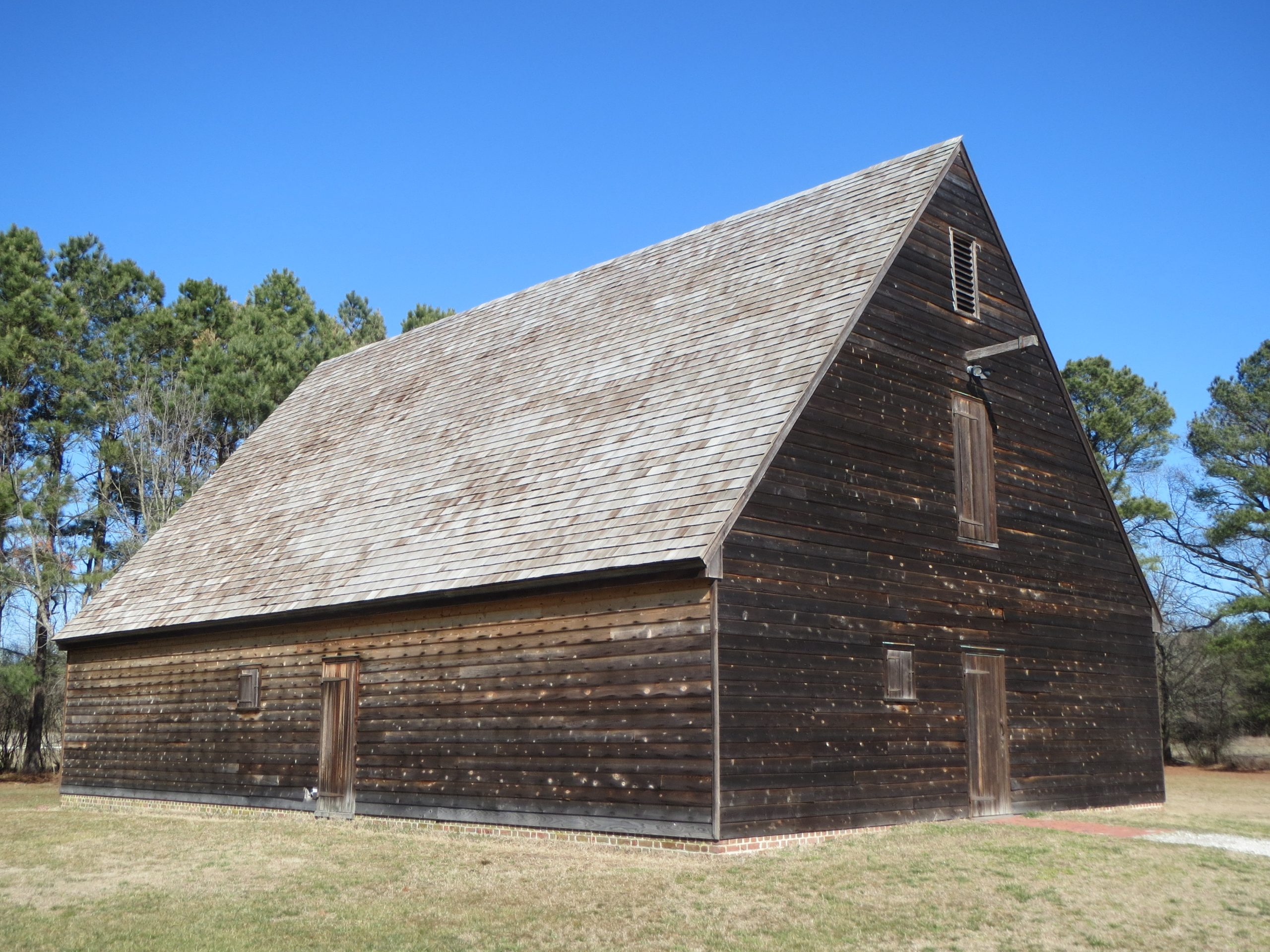 An image of a wooden farm building that is associated with Pemberton Hall, a home built in the mid-1700s. The buildings are now home to a museum and park.